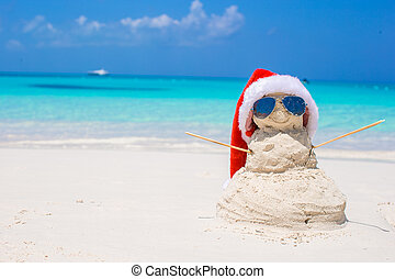Sandy snowman with red Santa Hat on white Caribbean beach -...