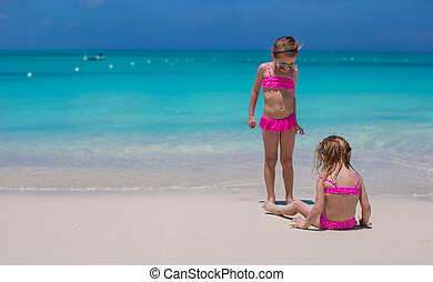 Little cute girls walking on white beach during vacation -...