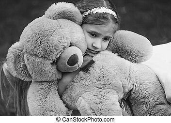 Monochrome portrait of small crying girl hugging teddy bear...