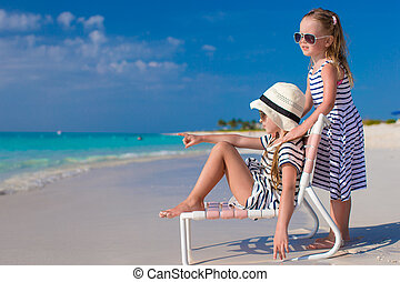 Little adorable girls in beach chair during caribbean...