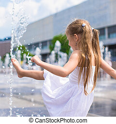 Little girl have fun in open street fountain at hot summer...