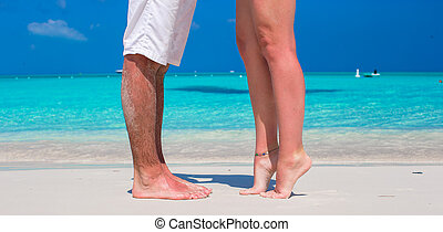 Close up male and female feet on white sand beach