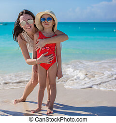 Mother and little girl at beach on sunny day