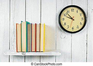 Watches and books on a wooden shelf.
