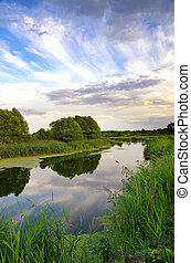 Summer landscape with the sky and clouds reflecting in the river