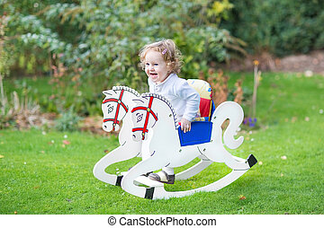 Cute happy litlte girl on a rocking horse in the garden