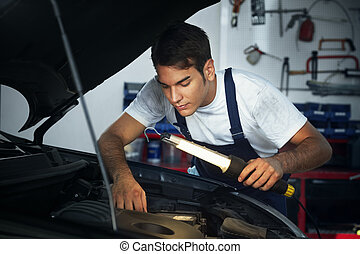 mechanic looking to car engine and holding lamp