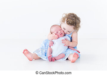 Sweet toddler girl kissing her newborn baby brother
