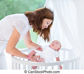 Young beautiful mother putting her newborn baby into a white rou