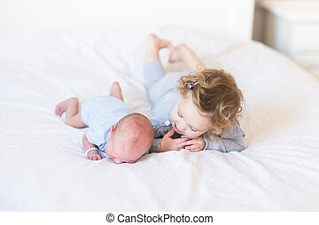 Sweet toddler girl supporting her newborn baby brother...