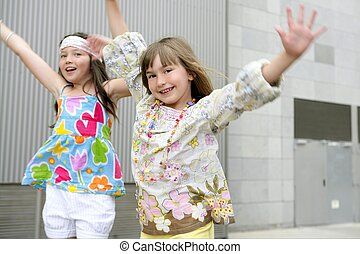 Two little girls dancing in the city with gray building in...