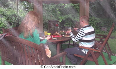 woman and man in bower - woman with man sit near table with...