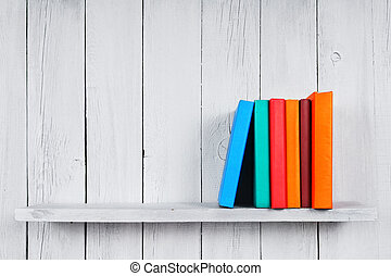 Books on a wooden shelf On a wooden, white background