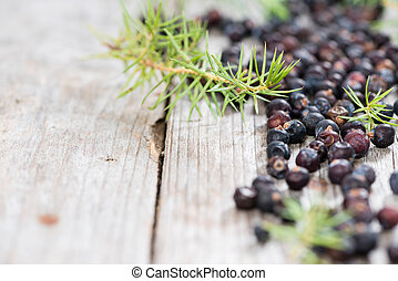 Dried Juniper Berries on wooden background (close-up shot)