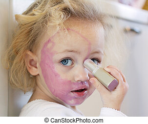 child covered in lipstick - a child painting her face with...