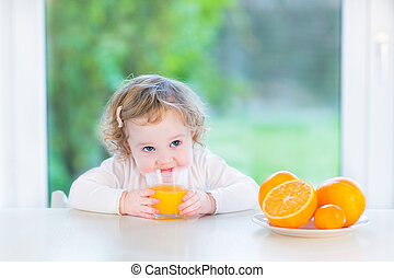 Cute little toddler girl drinking orange juice sitting at a whit
