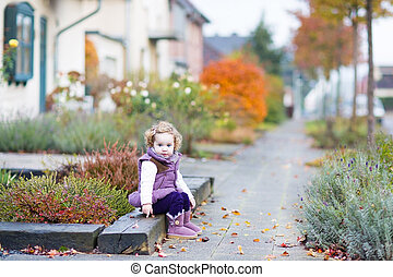 Little toddler girl with curly hair sitting on the front yard of
