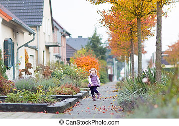 Cute toddler girl running on a beautiful street in a small...