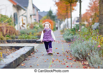 Adorable toddler girl walking down a beautiful road in a...