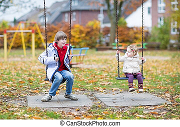 Laughing boy and his toddler sister playing together on a...
