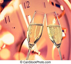 New Year or Christmas at midnight with champagne flutes make...