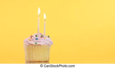 tasty birthday cupcake with candle, on yellow background -...