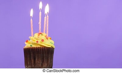 tasty birthday cupcake with candle, on purple background -...