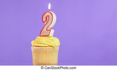 Birthday cupcake with candle number two. - Birthday cupcake...
