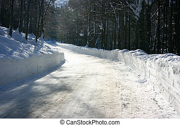 Winter road - Bending road in the forest covered by snow