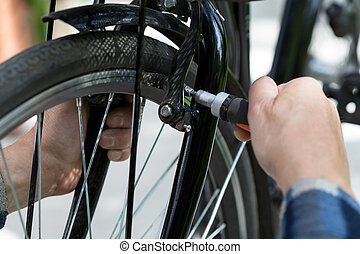Older man repairing a bicycle wheel on the outside