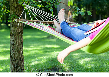 Lady lying with book on hammock - Young lady resting on...