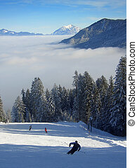 Skiing over the clouds - Ski track descending towards the...