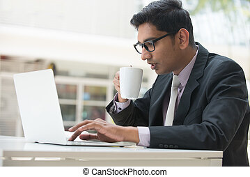 young indian business male on laptop and coffee at a cafe...
