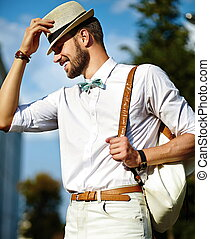 Young smiling stylish sexy handsome model man tourist in casual cloth lifestyle in the street in hat with bag