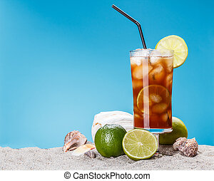 Iced sweet tea in sand with straw