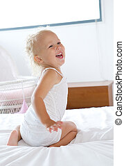 Baby girl laughing and playing in bed