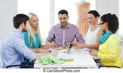 smiling fashion designers working in office - startup,...