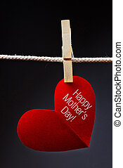Happy Mothers Day printed on red heart attached to rope with...