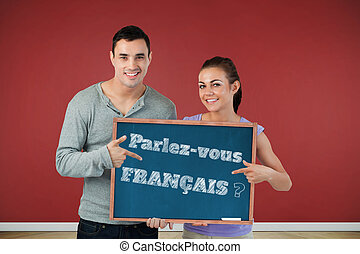Composite image of smiling young couple pointing at sign...