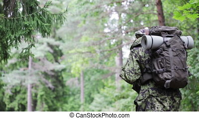 young soldier with backpack in forest - war, hiking, army...