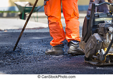 Asphalt surfacing manual labor. - Construction workers...
