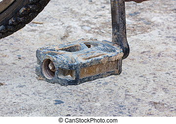 Detail of old used bicycle pedal with dry mud .