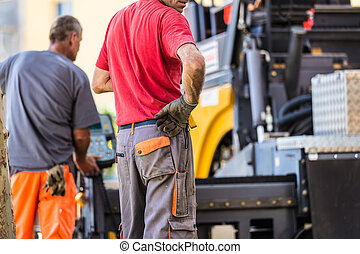 Asphalt surfacing manual labor - Construction workers during...