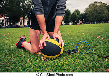 Woman with medicine ball and resistance band - A young woman...