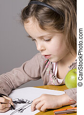 Little girl drawing with green apple