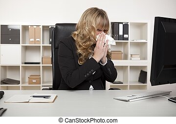Businesswoman blowing her nose at her desk - Businesswoman...
