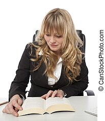 Young businesswoman sitting reading at her desk from a large...