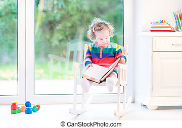 Cute little toddler girl reading a book in a white rocking chair