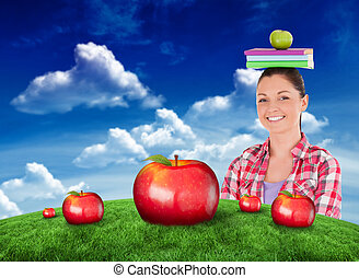 Composite image of pretty student holding an apple and books...