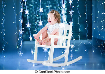 Happy laughing toddler girl playing in a white rocking chair...